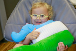 Young girl hugging the stuffed toothbrush in a treatment chair