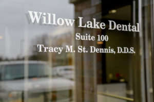 Photo of the front door with Willow Lake Dental and Tracy M. St. Dennis, D.D.S. stenciled in white paint